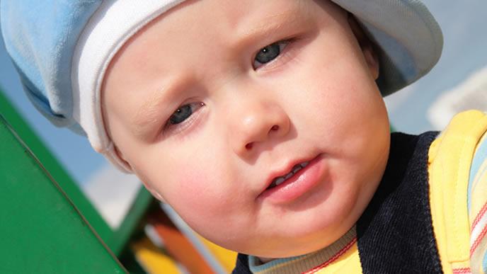 家族でおでかけしている青の帽子が似合う赤ちゃん
