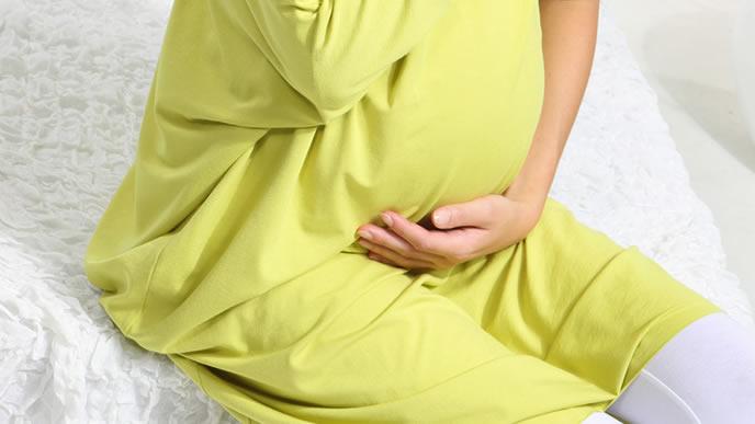 お腹をさすって胎動の痛みを和らげる妊婦