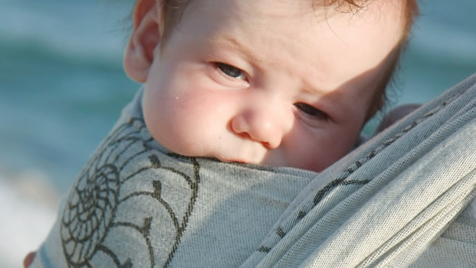 寝起きでぼーっとしているスリングの中の赤ちゃん