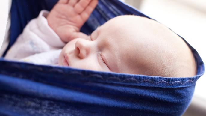 ママとおでかけするスリングの中の新生児