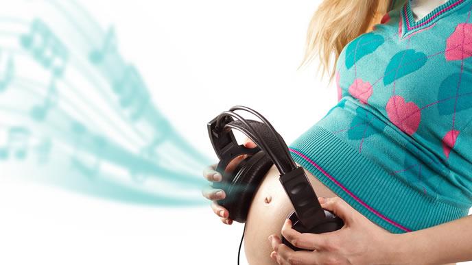 ヘッドフォンで胎動を確認する妊婦