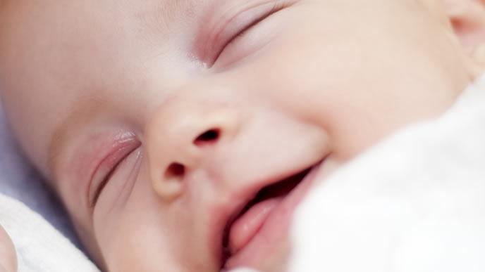 楽しそうな笑顔で寝る赤ちゃん