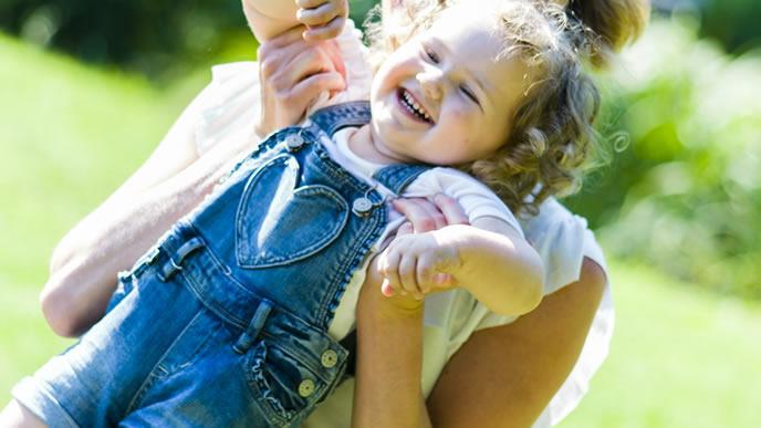 ママに抱っこされて笑顔の女の子