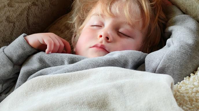 熱が下がらず寝込んでいる男の子