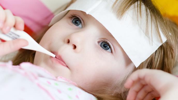 口で体温計を図っている女の子