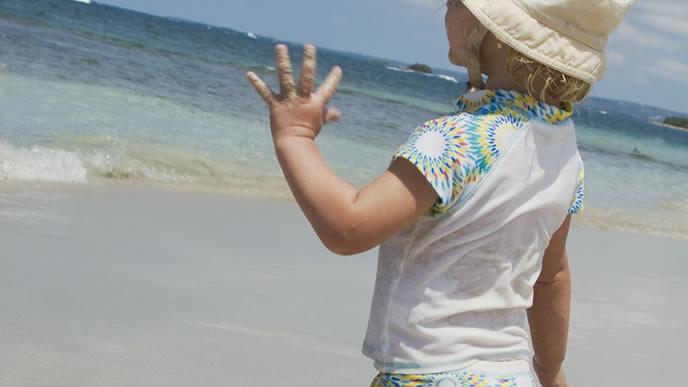 海で泳ぐパパに手を振る女の子