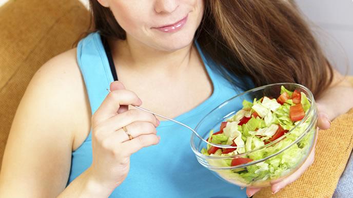 食欲が止まらずサラダを食べる妊婦