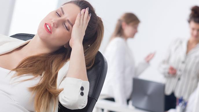 職場でつわりに苦しむ妊娠中の女性