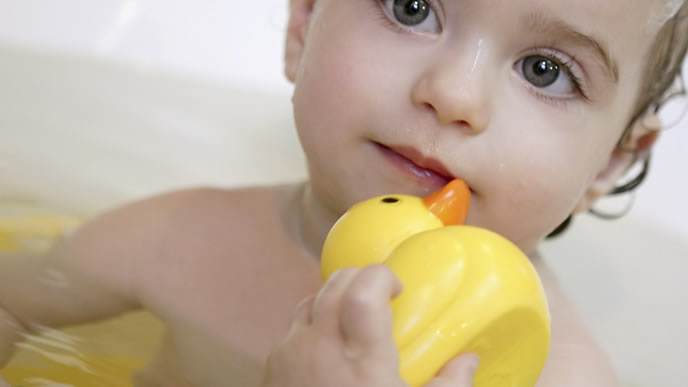 熱が下がりお風呂でアヒルと遊ぶ赤ちゃん