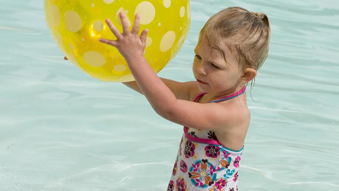 海でビニールボールを使い遊ぶ女の子