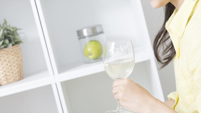 白ワイン片手に友達とお喋りする女性