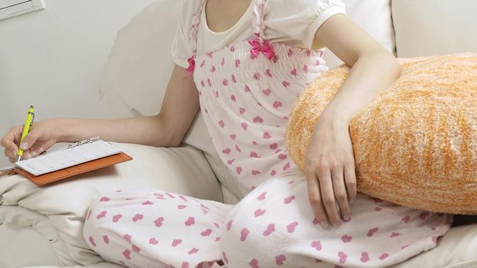 妊娠中の過ごし方をメモする女性