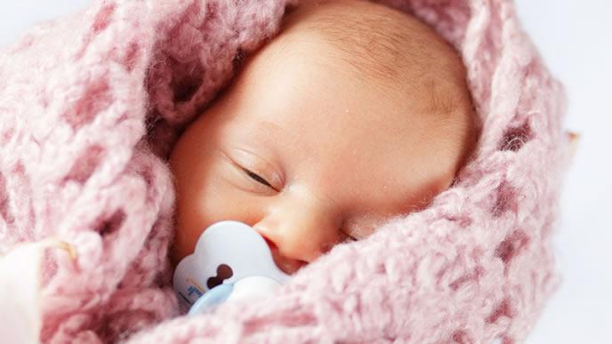 ニットのおくるみので熟睡する赤ちゃん