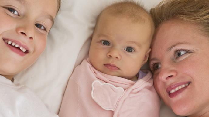 おくるみの中で目を見開く赤ちゃん