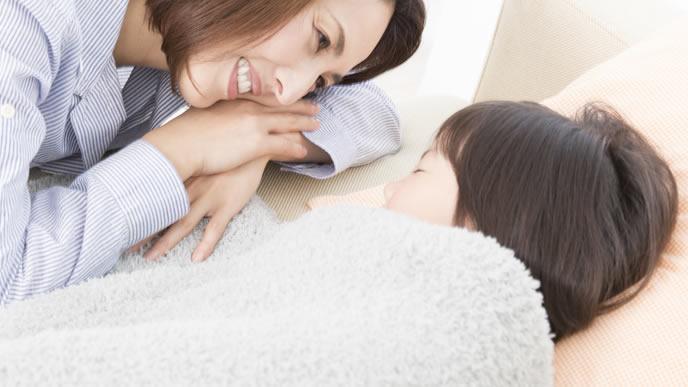 赤ちゃんの可愛い寝顔をみてほほ笑むママ