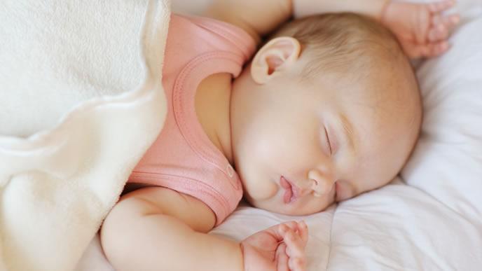 バンザイをしてスヤスヤ眠る赤ちゃん