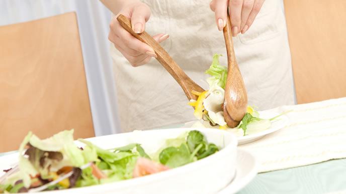 手作りの野菜サラダを取り分ける妊婦