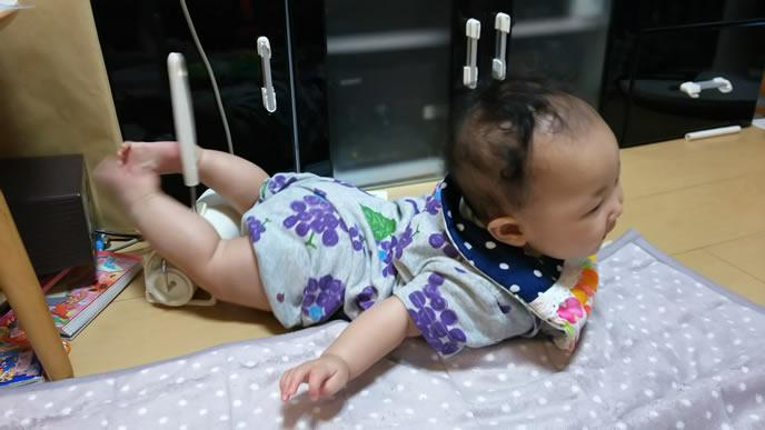コロコロを足で挟んで遊ぶ赤ちゃん