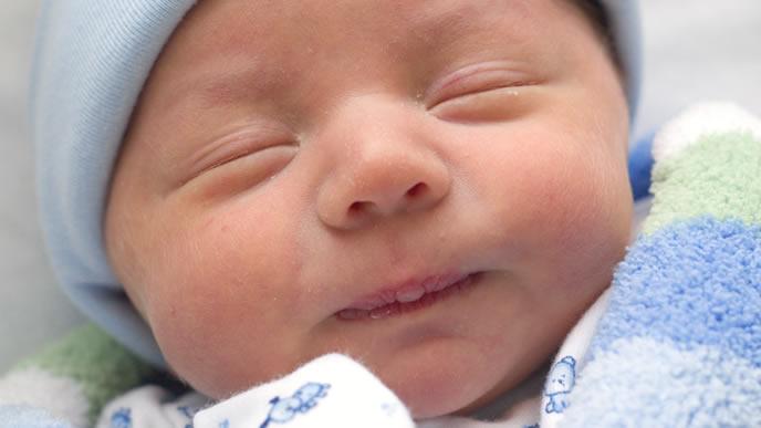 おくるみの中で安心して熟睡する赤ちゃん
