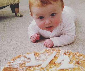ハーフバースデーのケーキを追いかける赤ちゃんの画像