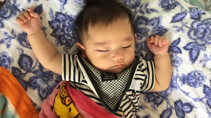 とびひが完治して両手を挙げる赤ちゃん
