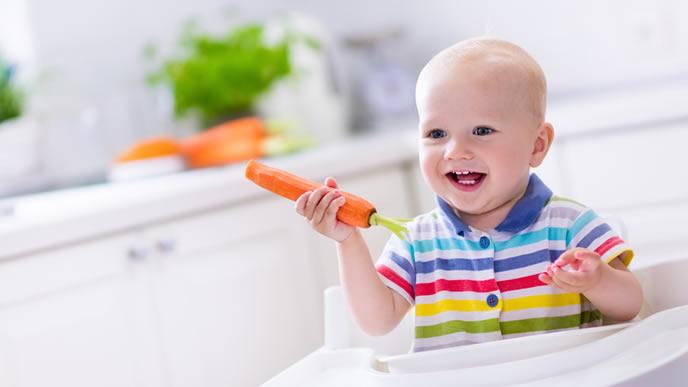 ニンジンを手に持ち離乳食を待っている赤ちゃん