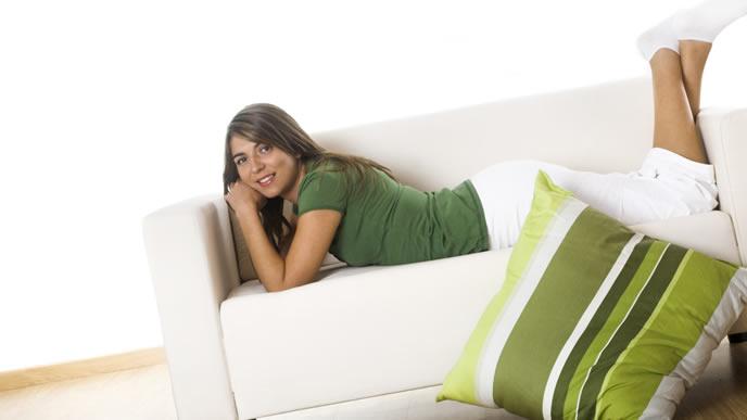 ベッドで横になりリラックスする妊婦