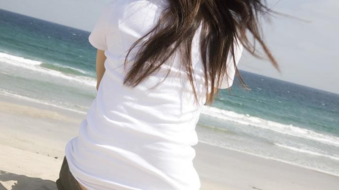 海を眺め体調変化を気に掛ける妊婦