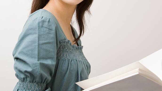 妊娠18週目の体の変化を本で確認する女性