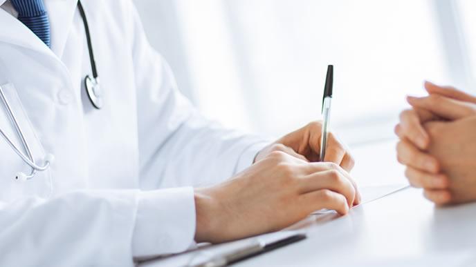 胸の痛みについて医師に相談する女性