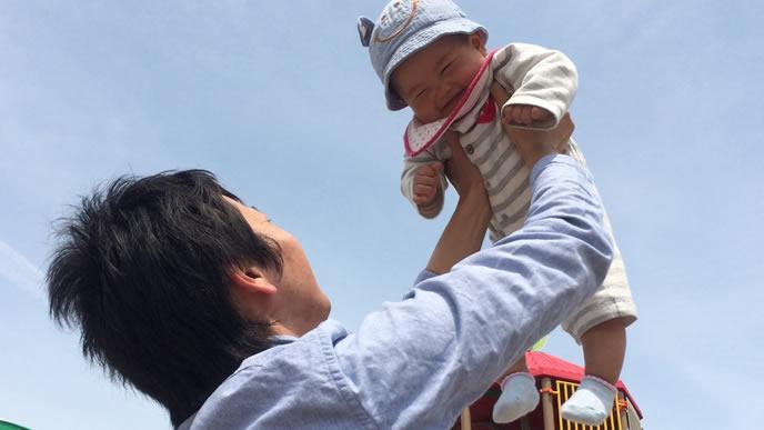 赤ちゃんを高い高いするイクメンパパ