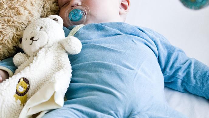 熱が下がりお気に入りのぬいぐるみと寝る赤ちゃん