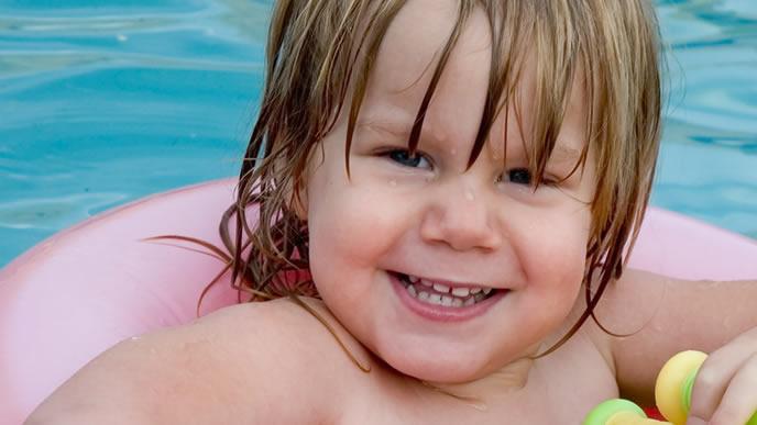 うきわでプールに浮く男の子