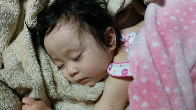 毛布に顔をつけて熟睡中の女の子