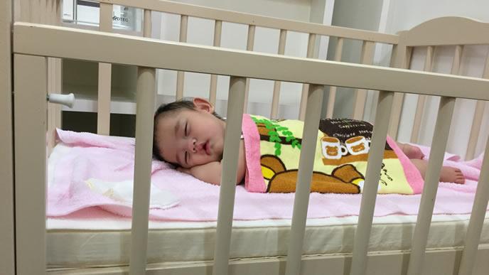 ベビーベッドで気持ちよさそうに眠る赤ちゃん