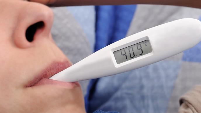 朝に基礎体温を計る女性