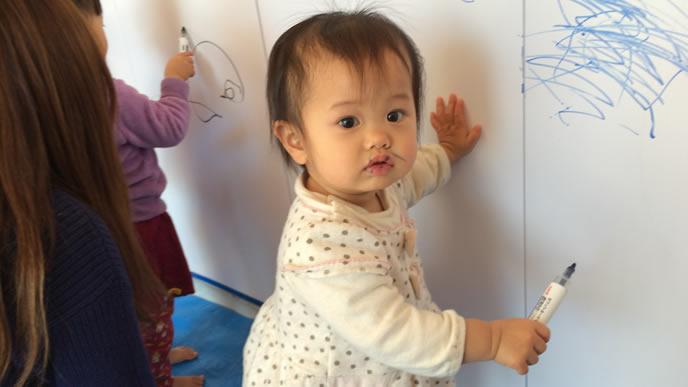 壁に落書きする赤ちゃん