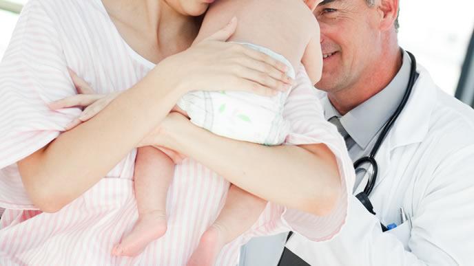 睡眠導入剤を口にした赤ちゃんを診察する医師