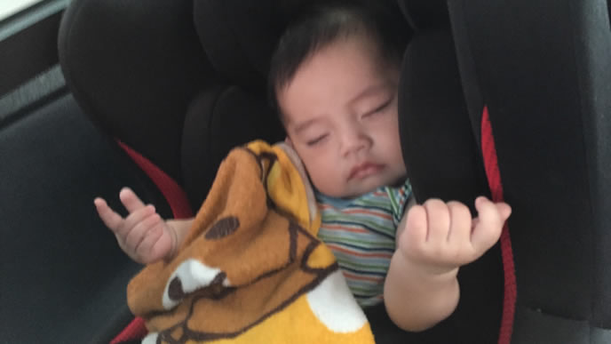 車の中で夢をみてポーズをとる赤ちゃん