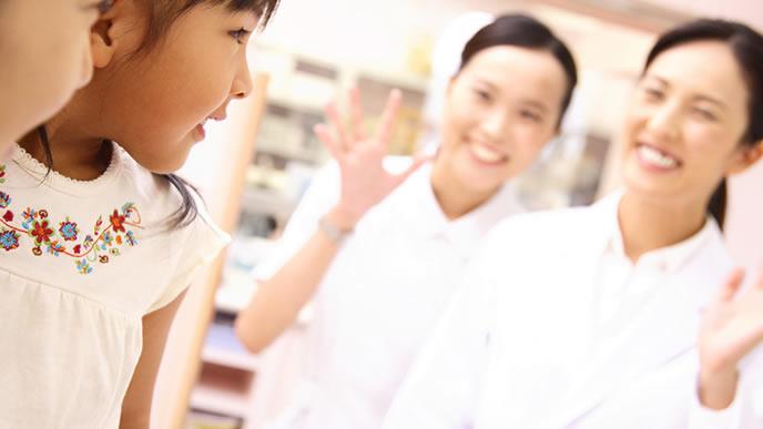 とびひの治療が終わった女の子に手を振る看護師