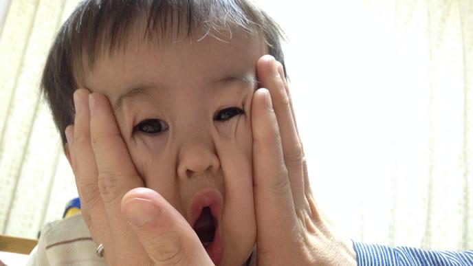 赤ちゃんの顔をギュとおさえイタズラするママ