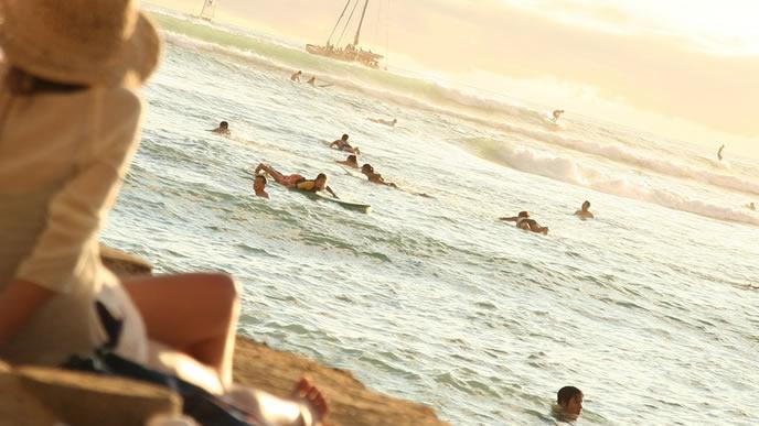 ハワイの海とサーファーを眺める女性