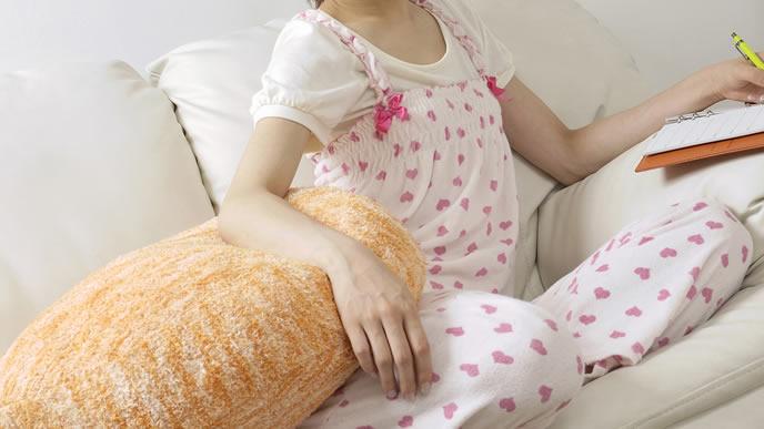 お腹の張りが辛くソファーで痛みを逃がす妊婦