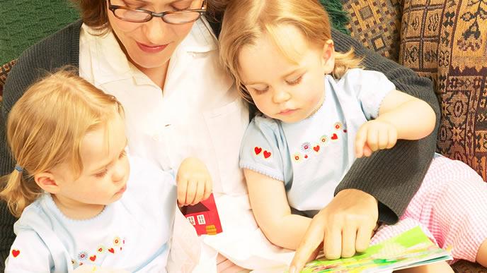 双子の赤ちゃんに絵本を読んであげるママ