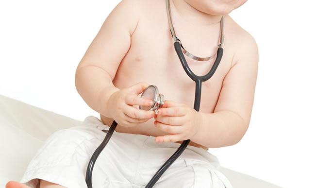 聴診器を手に持ちうなる原因を調べる赤ちゃん