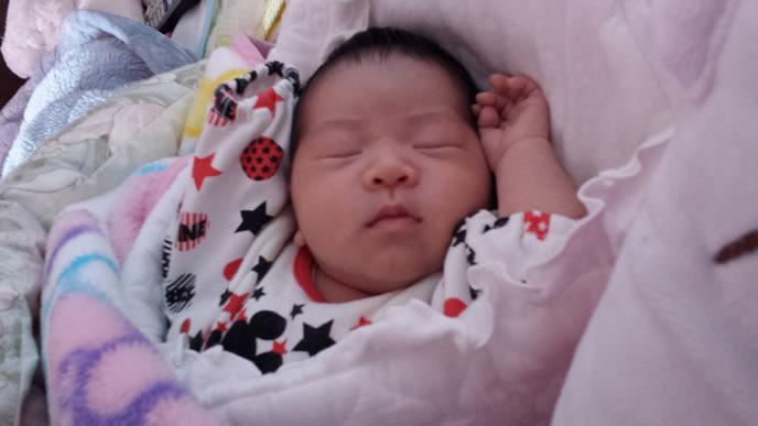 バンザイ寝でおやすみする赤ちゃん