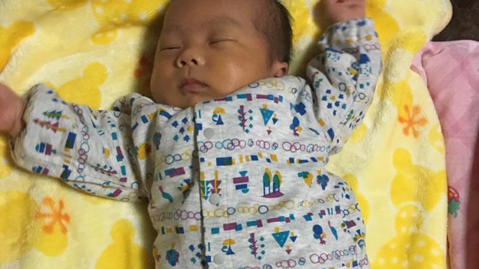 両手を伸ばしてぐっすり睡眠をとる赤ちゃん