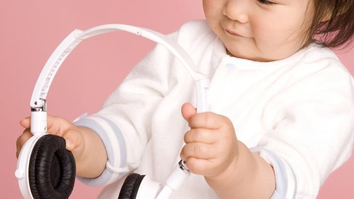 音楽が鳴るヘッドホンに興味が止まらない赤ちゃん