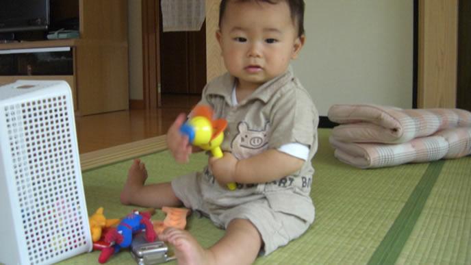 おすわりしながらカメラ目線の赤ちゃん