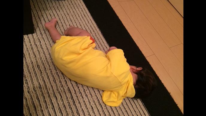 遊び疲れて眠る黄色い服の赤ちゃん